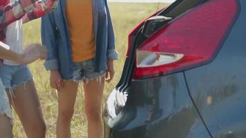 les femmes asiatiques ouvrent la porte arrière de la voiture avec des amis campant dans la nature ayant un voyage d'été. video