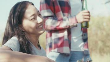 Young Asian woman with friends happy camping in nature having fun together playing guitar and drinking beer. video