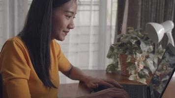 Asian woman smiling happy enjoying hands typing using laptop computer sharing online working blogger influencer. video