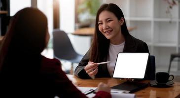 Reunión del equipo.Grupo de dos hombres de negocios que trabajan con un nuevo proyecto de inicio en la oficina moderna.Touch pad en manos de mujer foto