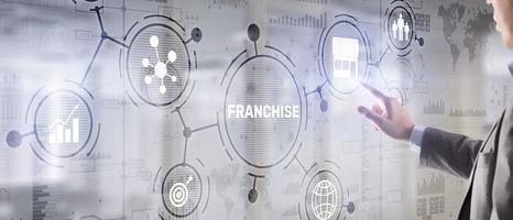 Businessman hand touching inscription Franchise marketing system photo