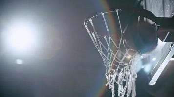 Basketball falling through wet net splashing water droplets in the night court in slow motion with light in the background video