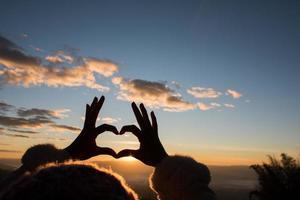 Manos de silueta formando una forma de corazón con la salida del sol foto