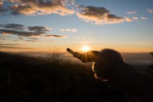 Silhouette of hand female holding sunlight photo