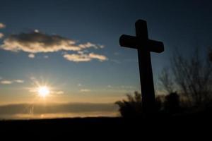 Silhouette of catholic cross and sunrise photo