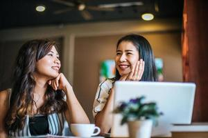 Two beautiful women talking everything together at coffee shop cafe photo