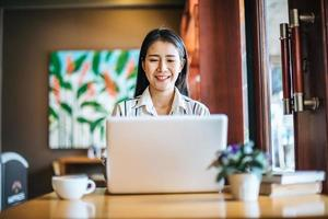 Beautiful woman working with laptop computer at coffee shop cafe photo