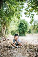 Happy boy sitting and thinking alone in the park photo