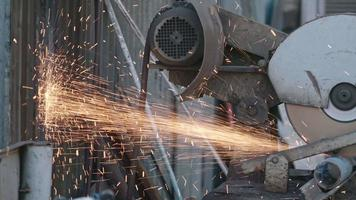 Side view of operating automatic grinder cutting metal with sparks flying around video