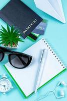 Vacation planning. Travel accessories on a blue background. Passport, sunglasses and notepad. photo