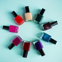 Group of bright colored nail polishes on blue background. Set of decorative cosmetics for body care. photo