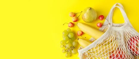 Ripe fruits in mesh bag on yellow background. Eco-Friendly cotton string bag for shopping. Organic dietary vegan foods. Banner format. photo