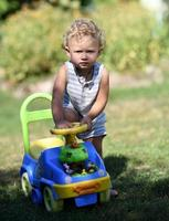 Beautiful baby boy with child toy car posing photographer photo