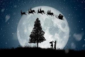 silueta de santa claus se mueven para montar en sus renos sobre la luna llena en la noche de navidad. disfrutando pareja bailando bajo la luna llena. foto