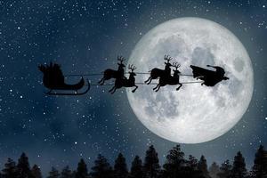 super santa claus man, un superhéroe volando sobre la luna llena guiando a sus renos en la noche de navidad. foto