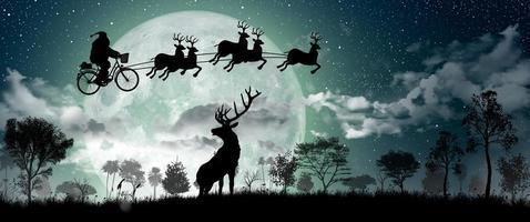 silueta de santa claus montando en su bicicleta para llevar un regalo con sus renos durante la luna llena en la noche de navidad. foto