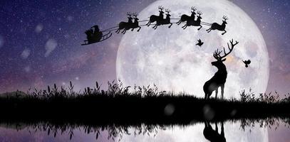silueta de santa claus volando sobre la luna llena. foto