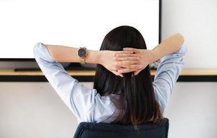 una mujer joven descansando para ver la televisión durante el fin de semana, el espacio en blanco de la televisión se puede insertar en texto o imágenes. foto