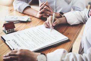 The customer holds a pen and reads the conditions in order to sign a house purchase contract with home insurance documents with the salesperson. photo