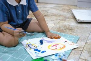 Concéntrese en las manos sobre el papel, el aprendizaje de la primera infancia mediante el uso de pinturas y pinceles para desarrollar la imaginación y mejorar las habilidades en la pizarra. foto