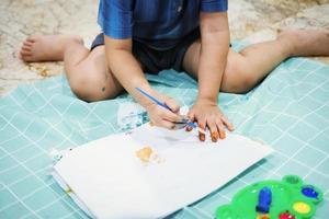 centrarse en sus manos sobre el papel. los niños usan pinceles para dibujar sus manos en el papel para desarrollar su imaginación y mejorar sus habilidades cognitivas. foto