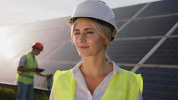 Beautiful female solar engineer standing near the panels and a young specialist in the background tests the batteries. Concept of green electricity video