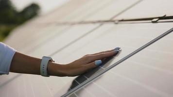 Close up of a young woman engineer hand is checking the operation of sun and cleanliness of photovoltaic solar panels on a sunset. Concept.renewable energy, technology, electricity video