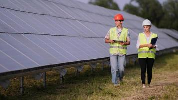 Two engineers are discussing drawings for the project. They are standing at a solar panel station. The female engineer teaches a young specialist who is undergoing practice video