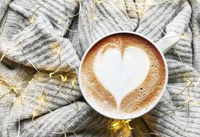 Coffee with a heart pattern on a warm knitted sweater photo