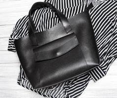 blusa a rayas y bolso de cuero negro foto