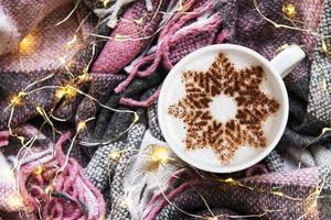 café con un patrón de copo de nieve sobre una cálida tela escocesa de lana foto