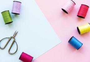 Lay Flat de rollos de hilo de colores y tijeras para coser en dos tonos de fondo, concepto de costura y costura. foto