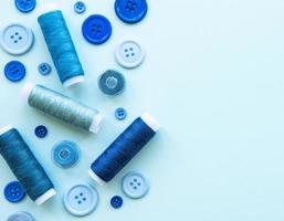 Spools of thread and buttons in blue tones on a blue background photo