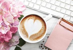 Home office desk workspace with pink hydrangea flower bouquet, cup of coffee and keyboard photo