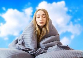 imagen creativa niña mujer en la cama después de dormir en el fondo del cielo aislado, dormir mujer, quedarse en casa concepto, cuarentena de coronavirus, despertar por la mañana foto