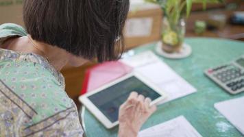 senior woman reading social media from digital tablet at terrace video