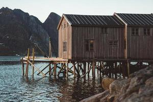 Old wooden fishing houses near lake against background of mountains photo