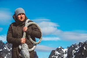 Man with a rope on his shoulder against background of mountains and blue sky photo