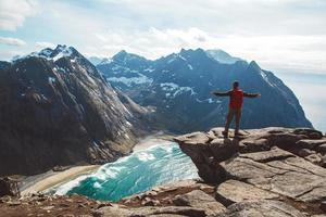 Man stand on cliff edge alone enjoying aerial view backpacking photo