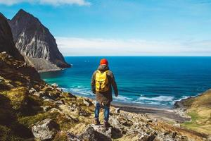 Man stand on cliff edge alone enjoying aerial view backpacking lifestyle travel adventure outdoor vacations photo