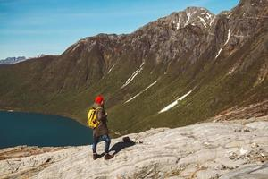 Man with a backpack standing on a rock on background of mountain and lake photo