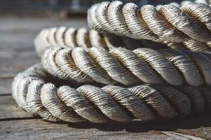 Close up of worn out thick mooring rope on wooden pier photo