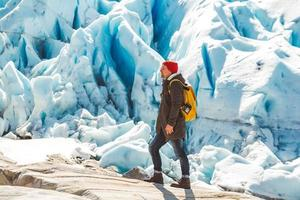 Man with backpack standing on a rock on background of a glacier and snow photo