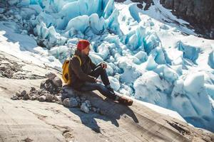 Man with backpack sitting on a rock on background of a glacier and snow photo