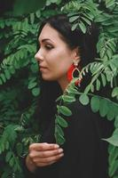 Woman in black dress and red decorations on background of forest photo