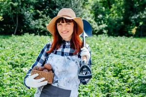 Woman farmer holds a potatoes in a wicker basket wearing a straw hat and surrounded by many plants in her vegetable garden photo