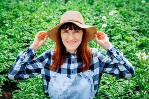 Retrato mujer campesina sonriendo a la cámara con un sombrero de paja en su huerto foto