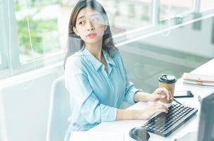 Retrato de joven mujer de negocios trabajando y mirando por la ventana foto