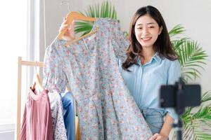 Retrato de una joven empresaria que está transmitiendo en vivo vendiendo ropa. foto