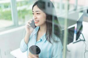 Retrato de mujer de negocios joven feliz hablando por teléfono foto